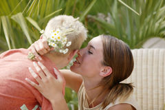 Young woman kissing little boy Stock Images