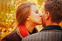 Young woman kissing a man in autumn park Stock Photo