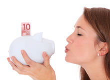 Young woman kissing piggy bank Royalty Free Stock Photos