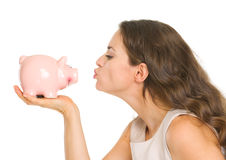 Young woman kissing piggy bank Stock Images