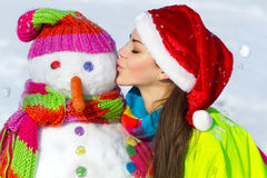 Young woman kissing a snowman Stock Photography
