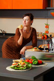 The young woman on kitchen Stock Images