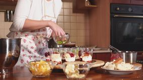 A young woman in an apron adds pieces of kiwi to plastic cups with vanilla cream. A young woman in a kitchen apron adds pieces of kiwi to plastic cups, where stock video footage