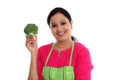 Young woman with kitchen apron holdong broccoli Royalty Free Stock Images