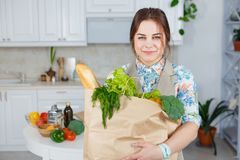 Young woman in the kitchen with a bag of groceries shopping.  Royalty Free Stock Photos