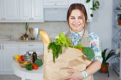 Young woman in the kitchen with a bag of groceries shopping.  Royalty Free Stock Photography