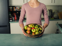 Young woman in kitchen with bowl of apples Royalty Free Stock Photos