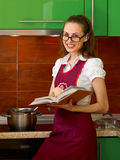 Young woman on kitchen with cook book Royalty Free Stock Photo