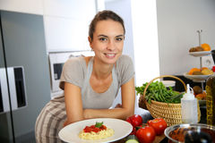 Young woman in kitchen cooking pasta Stock Photos