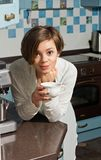 Young Woman on Kitchen Counter Holding Tea Cup Royalty Free Stock Images