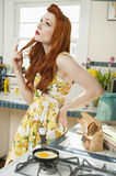 Young woman at kitchen counter thinking while looking up with hand on hip. Young women at kitchen counter thinking while looking up with hand on hip Stock Images