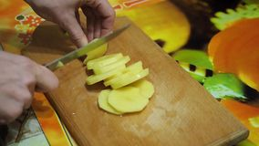 Young woman in the kitchen cutting the potatoes with knife on wooden cutting board stock video footage