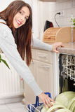 Young woman in kitchen doing housework. Puling out dishes from dishwasher Stock Images