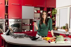 Young woman in the kitchen with glass of wine Royalty Free Stock Photo