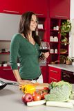 Young woman in the kitchen with glass of wine Royalty Free Stock Photos