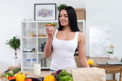Young woman in the kitchen having healthy breakfast, eating wholesome sandwich with vegetables and glass of milk front Stock Image