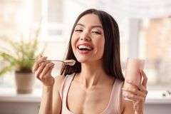 Young girl at kitchen healthy lifestyle standing with glass of shake looking camera laughing joyful stock photo
