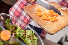 Young girl at kitchen healthy lifestyle standing putting cutted carrot into bowl close-up stock photography