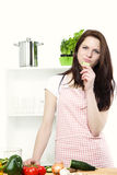Young woman in kitchen nibbling on a cucumber Royalty Free Stock Images