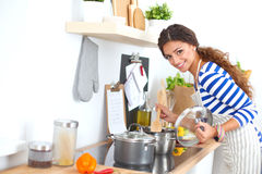 Young woman in the kitchen preparing a food Stock Photos