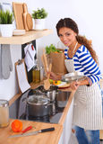 Young woman in the kitchen preparing a food Royalty Free Stock Photos
