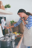 Young woman in the kitchen preparing a food Royalty Free Stock Image