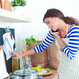 Young woman in the kitchen preparing a food Stock Images