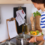 Young woman in the kitchen preparing a food Royalty Free Stock Photography