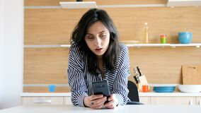 Young woman at the kitchen with a smartphone in hands. Browsing the web stock video footage