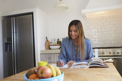 Young woman at kitchen table with recipe book writing a list Stock Photography