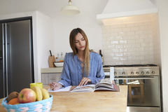 Young woman at kitchen table with recipe book writing a list Royalty Free Stock Photography