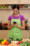 Young woman in kitchen and texting Stock Photography