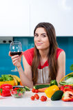 Young woman in the kitchen with a wine glass Royalty Free Stock Photos