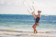 Young woman kite surfer getting ready for kiting on sand tropica Royalty Free Stock Photography