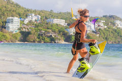 A young woman kite-surfer ready for kite surfing rides in blue s Stock Images