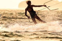A young woman kite-surfer rides Stock Photos