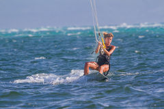 A young woman kite-surfer rides Stock Images
