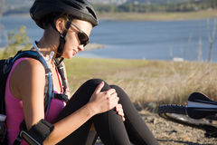 Young woman knee injury. Fall from a bicycle Royalty Free Stock Photo