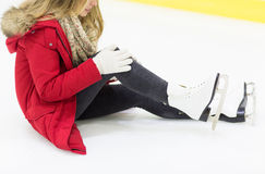 Young woman with knee trauma on skating rink. People, sport, trauma, pain and leisure concept - close up of young woman fell down on skating rink with knee Stock Image