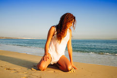 Young Woman Kneeling Down on the Beach Royalty Free Stock Images