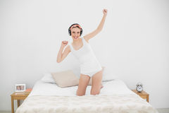 Young woman kneeling on her bed and listening to music Royalty Free Stock Photos