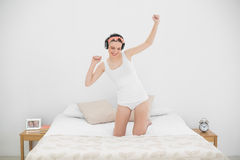 Young woman kneeling on her bed and moving while listening to music Royalty Free Stock Photography