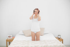 Young woman kneeling on her bed and wearing headphones Stock Photo