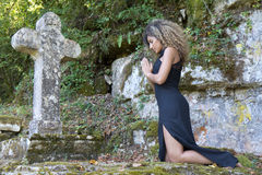 Young woman kneeling to pray. Young woman  kneeling in front of a stone cross. She is praying Royalty Free Stock Photography