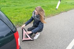Young woman kneels behind the car and mounts the warning triangle stock photos