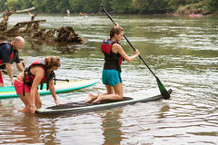 Young Woman Kneels On Paddleboard In Chattahoochee River. Atlanta, GA, USA - July 25, 2015: A young woman kneels on a paddleboard as she gets a push into the royalty free stock images