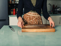 Young woman with knife and chopping board Royalty Free Stock Photography