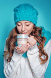 Young woman in knit scarf and hat drinking hot tea Stock Photography