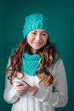Young woman in knit scarf and hat listening to music on headphon Stock Images