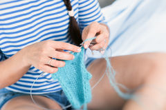 Young woman   knits. Close-up A young woman with dark hair braided in a braid, in a striped sweater and denim shorts knits a bare scarf from natural white Stock Photography